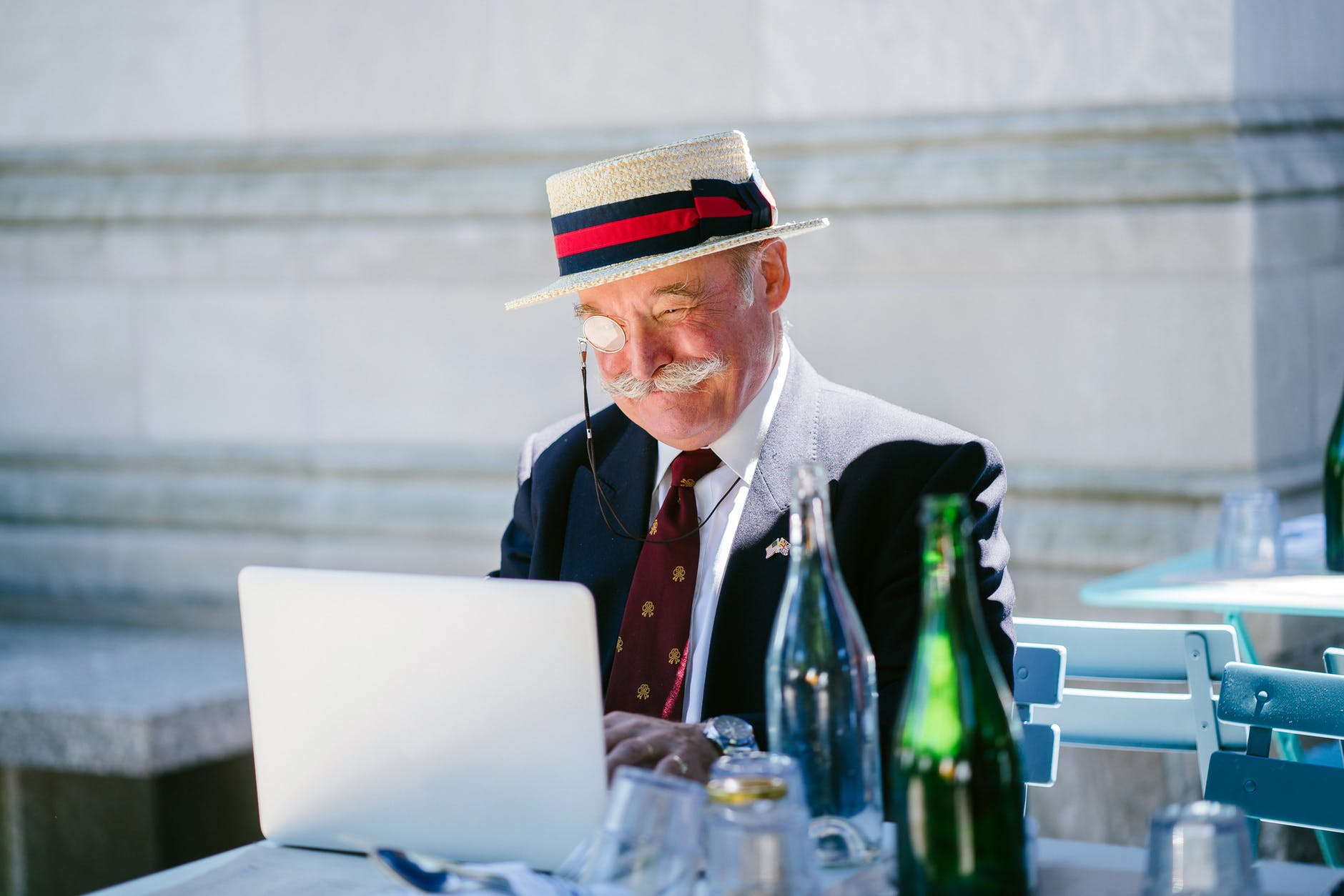 older eccentric man using laptop at a restaurant outdoors